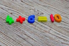 Mathebeispiel mit Farbe nummeriert auf einem hölzernen Hintergrund Lizenzfreies Stockfoto