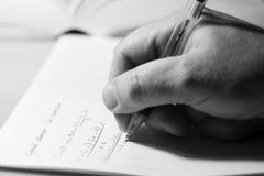 Mathematical equation man writing A. Photograph of a man writing a mathematical equation royalty free stock images