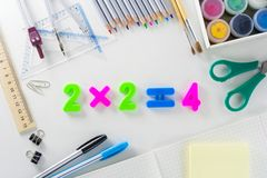 The mathematical equation `2*2=4` from plastic numbers on a white background with school articles. The mathematical equation `2*2=4` from multicolour plastic stock photos