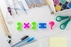 The mathematical equation `2*2=?` from plastic numbers on a white background with school articles. The mathematical equation `2*2=?` from multicolour plastic stock photo