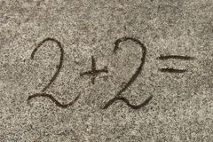 Mathematical equation. two plus two on sand. Background royalty free stock photo