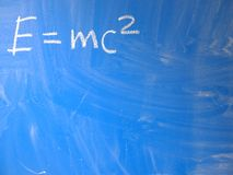 Mathematical formula e=mc2 squared written on a blue, relatively dirty chalkboard by chalk. Located in the upper left corner of. The image making space for some stock photos
