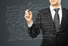 Mathematical formulas. Businessman drawing mathematical formulas on a gray background Stock Images