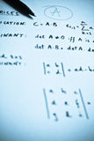 Mathematical formulas written on a white paper Stock Photo