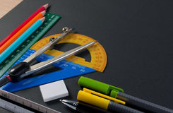 Mathematical instruments over the corner of black paper with copy space for text. Stock Photo
