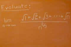 Mathematical problem. On orange chalkboard Royalty Free Stock Image