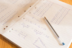 Mathematical sums written on pad paper. A series of mathematical sums written on two pages of pad paper. A single pen rests on the right hand page Royalty Free Stock Photos