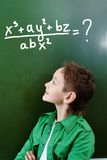 Mathematician. Portrait of smart lad looking at blackboard with algebraic formula on it Royalty Free Stock Photo