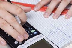 Mathematics. Student solving a trigonometry problem using a calculator Royalty Free Stock Image