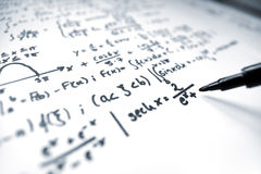 Mathematics. A macro image of a pencil writing math equations on a sheet of paper royalty free stock photos