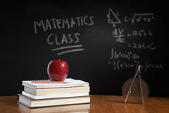 Mathematics class concept. With red apple on pile of books and drawing compass with equation on blackboard stock photos