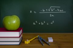 Back To School , a green apple on a Pile of Books in front of a. Mathematics class concept with green apple on pile of books and drawing compass with equation on royalty free stock photos