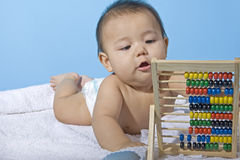Mathematics genius. Small charming baby with a calculating machine Stock Images