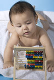 Mathematics genius. Small charming baby with a calculating machine Royalty Free Stock Photos