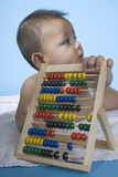 Mathematics genius. Small charming baby with a calculating machine Royalty Free Stock Photography