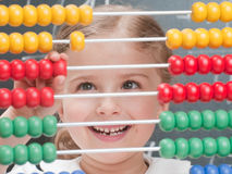 Mathematics lesson. Little girl is counting on an abacus during the lesson of mathematics royalty free stock photography