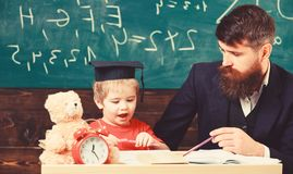 Mathematics lesson concept. Father teaches son mathematics. Teacher in formal wear and pupil in mortarboard in classroom royalty free stock photo