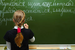 The schoolgirl writes chalk on a blackboard Stock Image