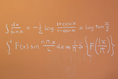 Mathematics on orange chalkboard Royalty Free Stock Images