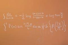 Mathematics on orange chalkboard Royalty Free Stock Images