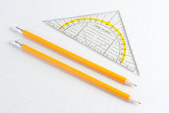 Mathematics ruler and pencils on squared paper Stock Photos