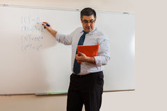 A mathematics teacher writes on a blackboard. New material for students. A lesson in the classroom Stock Images