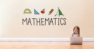 Mathematics text with little girl using a laptop computer. On floor Stock Photo