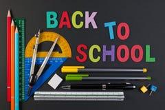 Mathematische Instrumente über der Ecke des schwarzen Papiers mit Text zurück zu Schule stockbild