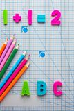 Mathematisches Beispiel und englische lateinische Buchstaben des Alphabetes färbten Bleistifte Stockfoto
