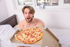 Mathemsändning Man den skäggiga stiliga grabben som äter ostliknande mat för frukost i säng Mannen gillar pizza för frukost arkivfoto
