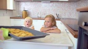 Mather bierze gorących ciastka od piekarnika na tło małych dziewczynkach ono uśmiecha się i jest szczęśliwy w domowej kuchni w do zdjęcie wideo