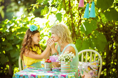 A mather and daughter hold hands and look to each other in the garden. A mather and a daughter hold hands and look to each other in the garden Stock Photography