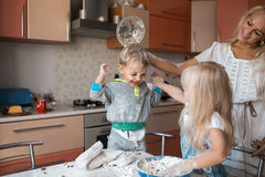 Mather daughter and son haveing fun on a kitchen. Mather have fun with kids on kitchen Stock Photo