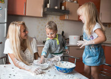 Mather daughter and son throws flour in each other. Mather have fun with kids on kitchen Royalty Free Stock Photos