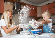 Mather and daughter throws flour in each other. Mather have fun with kids on kitchen royalty free stock images