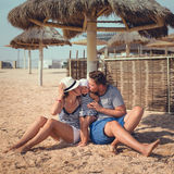 Mather and father at the beach with his daughter. Mather and father kissing their little daughter at the beach Royalty Free Stock Image