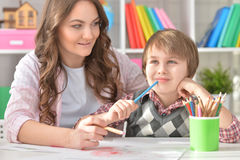 Mather and her little son drawing. With colorful pencils Royalty Free Stock Photo