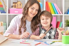 Portrait of a mother and son drawing. Mather and her little son drawing with colorful pencils Royalty Free Stock Photos