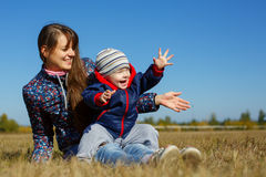 Mather hermoso joven feliz con el bebé en la naturaleza al aire libre Imágenes de archivo libres de regalías