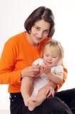 Mather im orange T-Shirt mit kleinem blondem Mädchen Lizenzfreie Stockfotografie