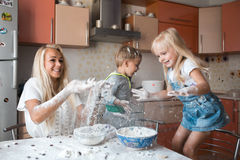 Mather and kids throw flour in the air. Mather have fun with kids on kitchen royalty free stock photography