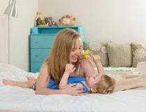 Mather playing with her son. Mother with her baby lying in bed , hugging his Stock Image