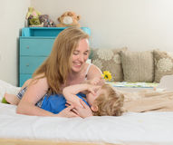 Mather playing with her son. Mother with her baby lying in bed , hugging his Stock Photos