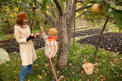 Mather and son near apple tree in garden. Mather and son near the apple tree in autumnal garden Royalty Free Stock Photos