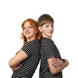 Mather and son stand back to back on gray. Redhead women and teenage boy in similar t-shirts stand back to back and smile isolated on white background in square Royalty Free Stock Photography