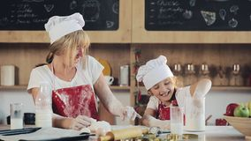 Mather tem o divertimento com a filha na cozinha Que preparam o cookiesand do Natal derramam a farinha na tabela Dia da família vídeos de arquivo