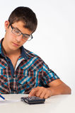 Maths. Teenager working with his calculator on maths exercises Royalty Free Stock Images
