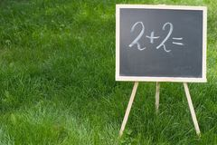 Maths. A chalkboard standing in the grass and with 2+2= written on it Stock Image