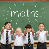 Maths against cute pupils showing thumbs up in classroom. The word maths against cute pupils showing thumbs up in classroom Royalty Free Stock Images