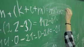 Maths' chalkboard. Hand's writing simple mathematical equation.  stock video